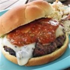 Horseradish Burgers - Grilled beef burgers are topped with distinctive Muenster cheese, and served with a zesty horseradish steak sauce mixture.