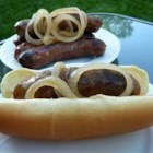 Wisconsin Slow Cooker Brats - Bratwurst are slow cooked in beer with onions and ketchup before being finished on a grill.