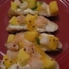 Shrimp and Mango Bruschetta - Slices of French bread are topped with Brie cheese and toasted before being finished with a sweet-and-spicy shrimp salsa for a refreshing summertime snack.
