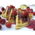 Eggnog-Raspberry Belgian Waffles - Eggnog added to waffle batter adds a touch of holiday flavor to these crisp Belgian waffles topped with warm raspberry preserves and fresh raspberries. Add a dollop of whipped cream if desired for a special Christmas breakfast or brunch.