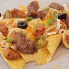 Brat Nachos - Nachos, Wisconsin-style, feature sliced bratwurst along with refried beans, browned onion, and cheese on warm tortilla chips. Serve with your favorite beer.