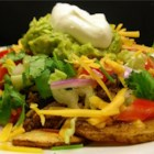 Mexican Potato Nachos - Potato slices form the base for a platter of hearty beef and bean nachos garnished with tomato, lettuce, sour cream, and guacamole.