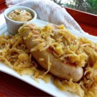 Beer Glazed Brats and Sauerkraut - A flavorful beer glaze coats bratwurst or knockwurst that are served atop a platter of sauerkraut for a German-inspired meal that's perfect with a cold beer.