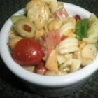 Conner's Birthday Pasta Salad - Tri-colored pasta is tossed with olives, kidney beans, garbanzo beans, Cheddar cheese, and Italian dressing for a light and easy side dish for parties or picnics.
