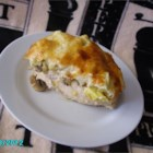 Artichoke Chicken Casserole - Chicken, mushrooms, and artichokes are baked under a layer of cheese and mayonnaise in this simple casserole dish.