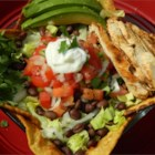 Grilled Chicken Taco Salad - Spice-rubbed grilled chicken breasts are served over a bed of lettuce, black beans, and salsa. Grilled corn tortillas make a smoky shell for this outstanding taco salad.
