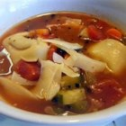 Italian Sausage Tortellini Soup - This delicious Italian soup features tortellini, sausage, and lots of vegetables -- carrots, tomatoes, zucchini, and bell pepper.  The soup is enriched with beef stock and red wine, and garnished with grated Parmesan cheese.