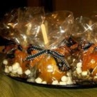 Rocky Road Caramel Apples - Caramel apples are taken down a rocky road by rolling in marshmallows and pecans. A dark chocolate drizzle finishes them off.