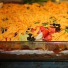 Healthier Seven Layer Taco Dip - By using low-fat cheeses, no-fat-added refried beans, and increasing the amount of peppers, this is a healthier version of everyone's favorite seven layer dip. Bring this to parties as a treat for friends.