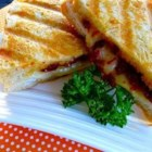 Turkey and Sun-dried Tomato Panini - Turkey, provolone cheese, and sun-dried tomatoes are sandwiched between two slices of bread in a panini maker for a savory, flavorful lunch.