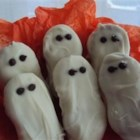 Halloween Ghosties - Peanut butter sandwich cookies are dipped in white chocolate and given two little ghostly eyes made out of chocolate chips.