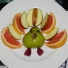 Sheri's Fun Fruit Turkey - Here's a fun way to serve fruit to the kids for Thanksgiving. Pears are cut in half to make turkeys, raisins and dried apricots form the faces and feet, a couple of walnut pieces make the wattles, and sliced apples and mandarin orange sections are arranged into a fan of tail feathers.