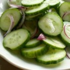 Crisp Marinated Cucumbers - Sliced cucumbers and sweet onion marinate in a sweet and tangy combination of vinegar and sugar in this refreshing salad.