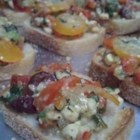 Roasted Red Pepper and Feta Bruschetta - Toasted baguette slices are broiled with a savory topping of feta cheese, Greek olives, tomato, and roasted red pepper for a Mediterranean-style appetizer they'll love.