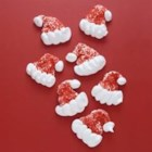 Santa Hats - Adorable little meringue Santa hat cookies are colored red with white pom-poms and trim. They're gluten-free so everybody can enjoy them.