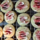 White Chocolate Raspberry Thumbprint Cookies - Raspberry thumbprint cookies get a drizzle of white chocolate and a sprinkling of red sugar for a festive Christmas cookie perfect for gifts or parties.