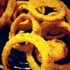 Southern-Style Onion Rings - Cornmeal gives these deep-fried onion rings a bit of crunch with their crispness in a zesty breading with authentic Southern flair.
