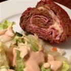 Quick and Easy Sicilian Meatloaf - This savory ground beef meatloaf is made in a roll shape with a layer of deli ham and Swiss cheese hidden inside.