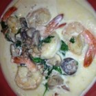 Grits a Ya Ya - Bacon, spinach, and mushrooms come together with jumbo shrimp in a creamy sauce served over a platter of smoked Gouda cheese grits.
