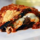 Eggplant Parmesan with Fresh Basil and Smoked Mozzarella - A gourmet version of the Italian-inspired favorite dish has plenty of fresh basil, smoked mozzarella cheese, and rich marinara sauce covering delicious fried eggplant slices.