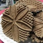 Italian Pizzelles - Italian Crisp Wafer cookies made with a patterned iron. This recipe has chocolate and ground nuts. These are also good when topped with your favorite chocolate icing.