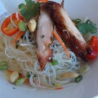 Spicy Rice Noodle Salad - Grilled chicken thighs top this main dish salad that showcases the spicy and sweet flavors of Thai food. Toss with fresh herbs, vegetables, and crunchy peanuts for a simple and light-tasting meal.