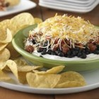 Layered Black Bean Dip - Black beans, spicy diced tomatoes, and shredded cheese on a base of cream cheese make a crowd-pleasing dip for chips and fresh veggies.