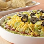 PHILADELPHIA(R) 7-Layer Mexican Dip - So easy to make and eagerly eaten, this classic layered dip uses spicy cream cheese, guacamole, salsa, cheese, lettuce, and olives for a true crowd pleaser.