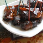 Candied Bacon Pigs - Little smoked sausages are wrapped in bacon and slow-cooked for hours in brown sugar, cola, and a touch of five-spice powder for a great appetizer that looks after itself.