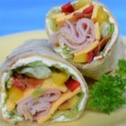 Kickin' Turkey Club Wrap - Spicy jalapeno cream cheese spread on tortillas is topped with turkey, bacon, avocado, and strips of red bell pepper in these quick snack or lunch wraps.