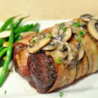 Bacon-Wrapped Venison Tenderloin with Garlic Cream Sauce - Venison tenderloins trimmed into roasts are wrapped in bacon slices, roasted, and served with a creamy mushroom sauce in this elegant recipe.