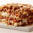 Louise's Lasagna - This lasagna gets cheesy with mozzarella cheese, cottage cheese, white American cheese, and Parmesan cheese. Adding salami and pepperoni sausage to ground beef in the tomato sauce adds yet more flavor.
