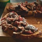 Parmesan Bruschetta with Mushroom Ragu - Lots of fresh and dried mushrooms simmered with Parmesan cheese and diced tomatoes top toasted baguette rounds for a sophisticated but easy appetizer.