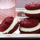 Red Velvet Sandwich Cookies - A delicious new way of serving Red Velvet cake--as a fun sandwich cookie. Tastes great and makes for a playful addition to any dessert tray.