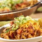 15-Minute Dinner Nachos Supreme - Taco-seasoned ground beef simmered with tomato and rice is topped with salsa, cheese and lettuce for a tortilla chip-dipping meal.