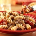 Beef and Pasta - This one-skillet dinner combines Swanson(R) Vegetable Broth, seasoned ground beef, garlic, tomatoes and corkscrew pasta that simmer together to make a quick and delicious dish.