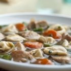 Chicken and Tortellini Stew - Diced chicken breast is browned and added to golden Swanson(R)  Chicken Broth, along with tender cheese-filled tortellini, carrots, onion and green beans.