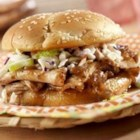 Down-Home Easy Barbecue Pork Rolls - Sliced roast pork simmers with in a hot and zesty barbecue sauce and is served North Carolina-style piled on sandwich rolls and topped with coleslaw.