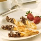 Chocolate-Dipped Spiced Twists - Pepperidge Farm(R) Puff Pastry Sheets are sprinkled with a mixture of ground crystallized ginger root and sugar, cut and shaped into twists, baked until golden, and then partially dipped in melted chocolate.