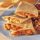 Cheesy Chicken Quesadillas - Flour tortillas filled with a spicy, creamy chicken mixture are browned until crispy and hot, and cut into wedges to serve.