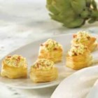 Artichoke and Sun-Dried Tomato Cheesecakes - Pepperidge Farm(R) Mini Puff Pastry Shells are filled with a savory 'cheesecake' filling featuring chopped artichoke hearts, minced sun-dried tomatoes, and Parmesan cheese to make mouthwatering appetizers.