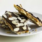 Ghirardelli(R) Chocolate Saltine Toffee - Transform saltine crackers into crunchy toffee by topping with homemade caramel, bittersweet chocolate, and sliced almonds. Enjoy the multi-layered texture and a symphony of sweet and savory.