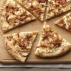 White and Gold Pizza - Melting cream cheese onto the crust of this 3-cheese pizza keeps the dough tender and provides a creamy sauce-like base for the caramelized onions and toppings.