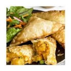 Vegetable Samosas - Peas, carrots and potatoes in a spicy red curry sauce are folded into wonton wrappers and fried until golden brown in this classic appetizer or side dish.