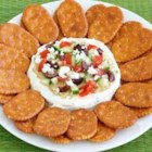 Greek Garden Spread - A cream cheese and yogurt layer is spread with hummus then topped with chopped cucumber, tomato, crumbled feta cheese, and olives in this Greek-inspired cracker spread.