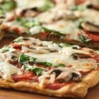 Grilled Spinach and Mushroom Pizza - Grilled pizza is easier than you think, and this spinach and mushroom veggie pizza recipe is a hearty and delicious one to try.
