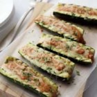 Grilled Stuffed Zucchini Boats - Scooped-out zucchini 'boats' are grilled with a creamy tomato-basil sauce and shredded cheese, and topped with parsley for a great summer barbecue side dish.