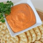 Creamy Roasted Red Pepper Spread - A creamy blend of roasted red peppers, parsley, garlic, and Parmesan and cream cheese is garnished with chopped parsley and served with crackers.