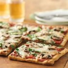 Mushroom-Pesto Grilled Pizza - The secret to perfect grilled pizza is to grill the crust first, then add the toppings. Serve one slice as an appetizer or two with a salad for a simple supper.