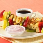 French Toast Fruit Kabobs with Dip - Strips of golden-brown French toast and chunks of your favorite fruit are threaded onto skewers then dipped in a fruity yogurt mix for a fun and tasty treat.